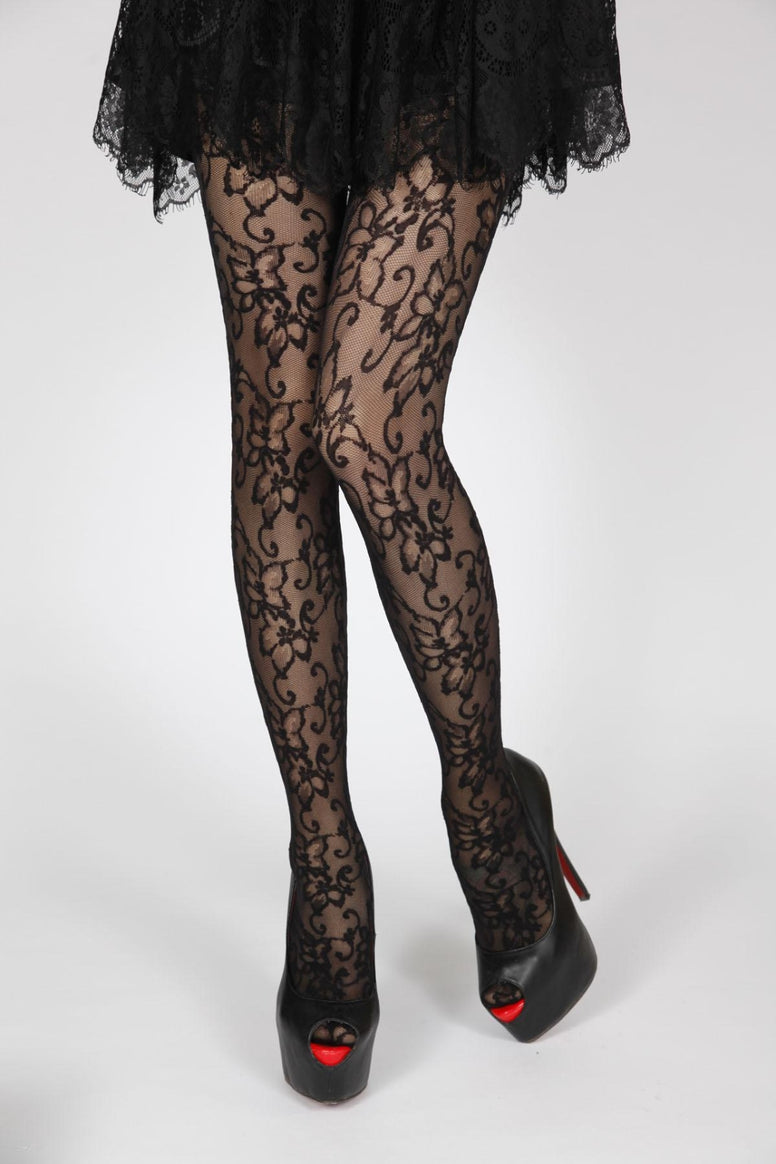 Lady wearing black lace floral tights with black frilly skirt and high heeled shoes.