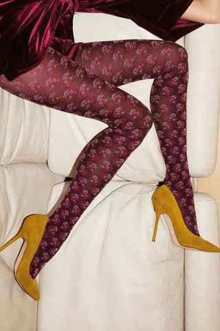 Clos up of lady's legs wearing bordeaux red flower print tights.