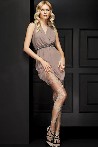 Lady standing with front leg bent wearing a short brown dress and rose pattern sheer tights.