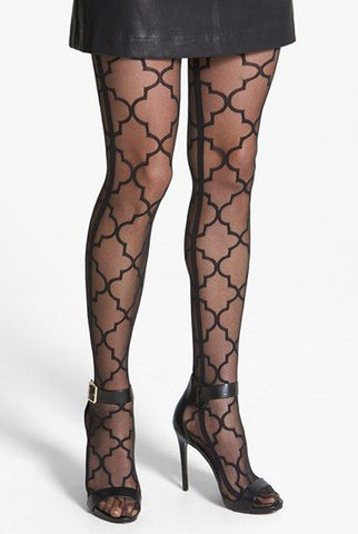 Front view of lady's legs standing wearing sheer black pattern tights, black heels and short black skirt.
