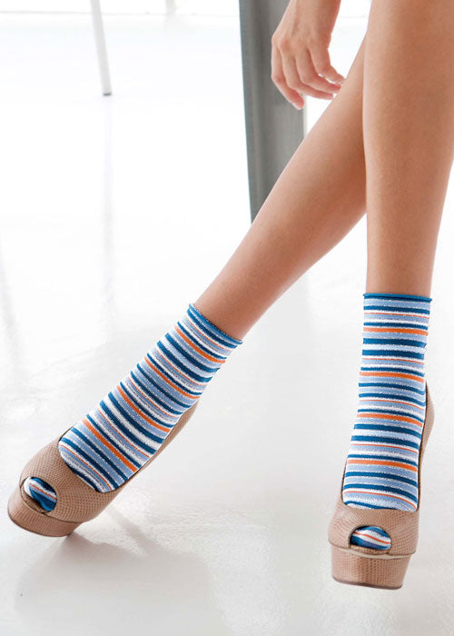 Close up of lady's feet wearing striped coloured socks.