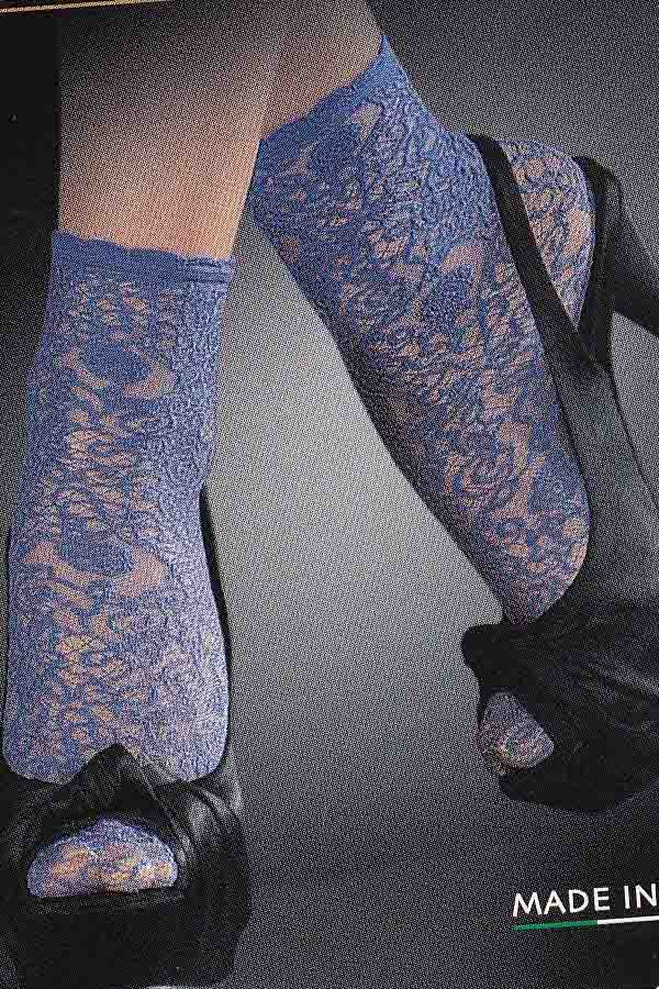 Close up of lady's feet in blue lace socks and black sandals.