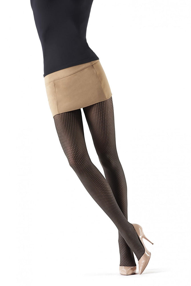 Front view of lady's legs standing, crossed at the ankles wearing beige mini skirt and pattern tights.