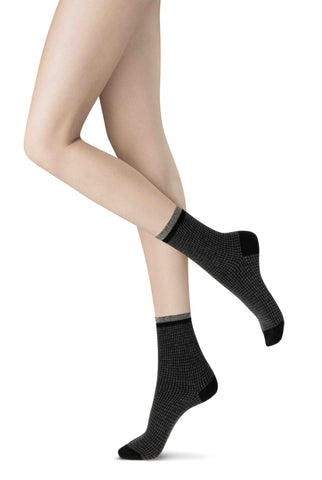 Side view of lady's feet in patterned black and grey ankle socks.