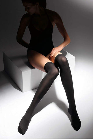 Lady sitting wearing long black over knee socks and a black top.