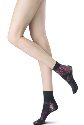 Side view of lady's legs and feet wearing short, black and purple flower print socks.