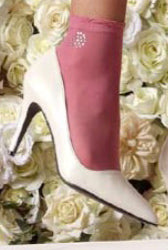 Lady's foot wearing pink crew socks with rhinestone appliqué` and white heels.