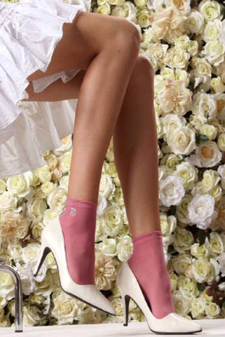 Lady's legs wearing pink short crew socks in front of floral back drop.