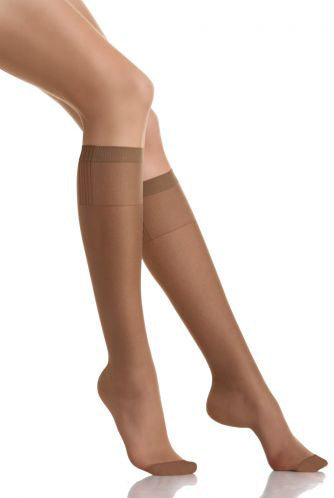 Lady's leg's outstretched wearing nude sheer knee highs.