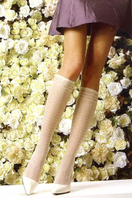 Lady's legs  in ivory knee highs standing in front of a floral backdrop.
