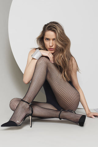 Lady resting a hand on her raised knee wearing black fishnets.