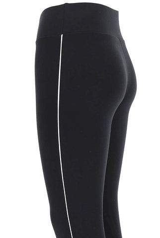 Close up of side view of waistband and upper thighs of lady's black and white leggings.