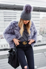model wears cashmere mini with fur pom pom in dark grey, with Dark grey ostrich feather jacket, liberty emma tshirt and gucci belt