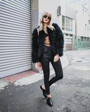Blonde model wears black faux fur jacket and leather pants