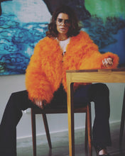 Model wears Bright Orange Ostrich Feather Jacket and 70's flared jeans