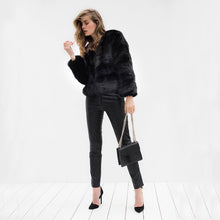 Model wears black faux fur jacket with black skinny jeans and holds black leather designer handbag