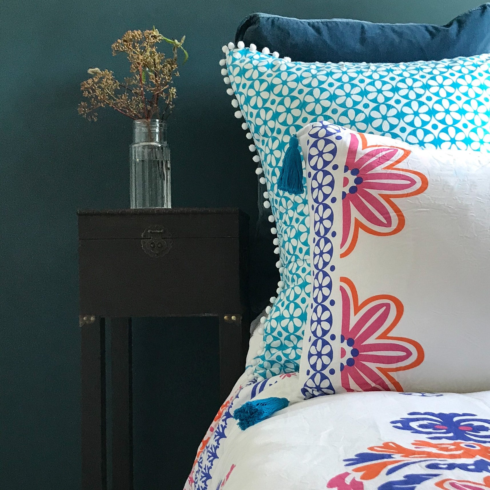 Orange, pink and blue stylised orchid motifs on crisp white luxury organic cotton pillowcases.  Finished with vivid blue removable tassels.