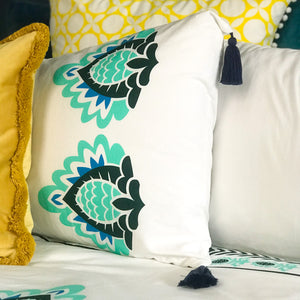 Luxury 300 thread count organic cotton pillowcases, printed with sea green and dark green floral elements with removable navy tassels.