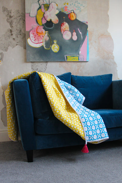 Luxury organic quilt printed in yellow geometric pattern, reversible side in blue geometric print.  Pink removable tassels for detail