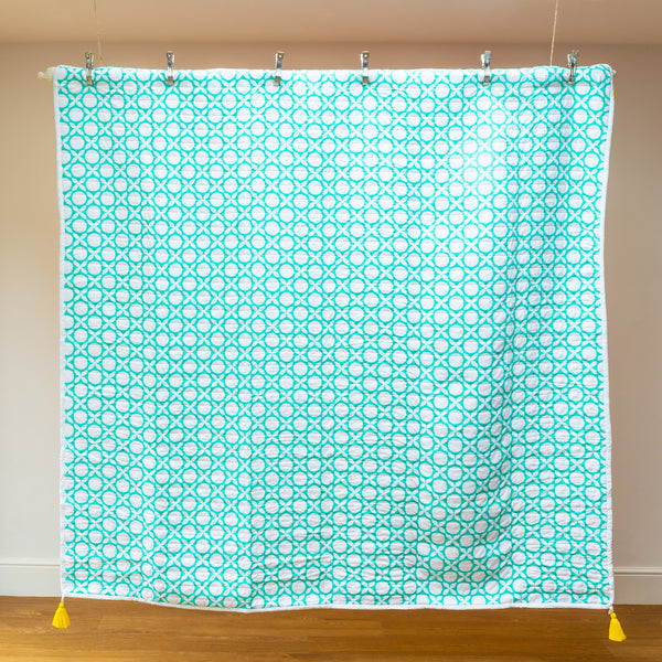 Gorgeous sea green geometric printed reversible organic quilt.  Yellow removable tassels for decoration