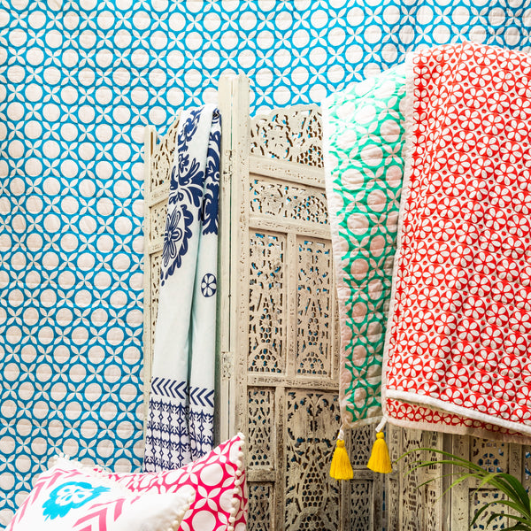Ruby forest quilt draped over a screen beautiful coral and sea green geometrics with white piping and removable yellow tassels