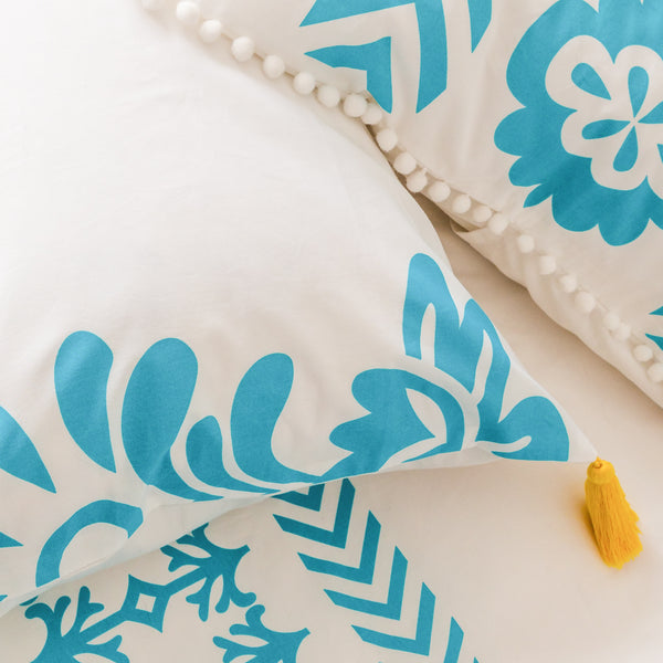 Bright aqua blue printed organic pillowcase with sunny yellow removable tassels