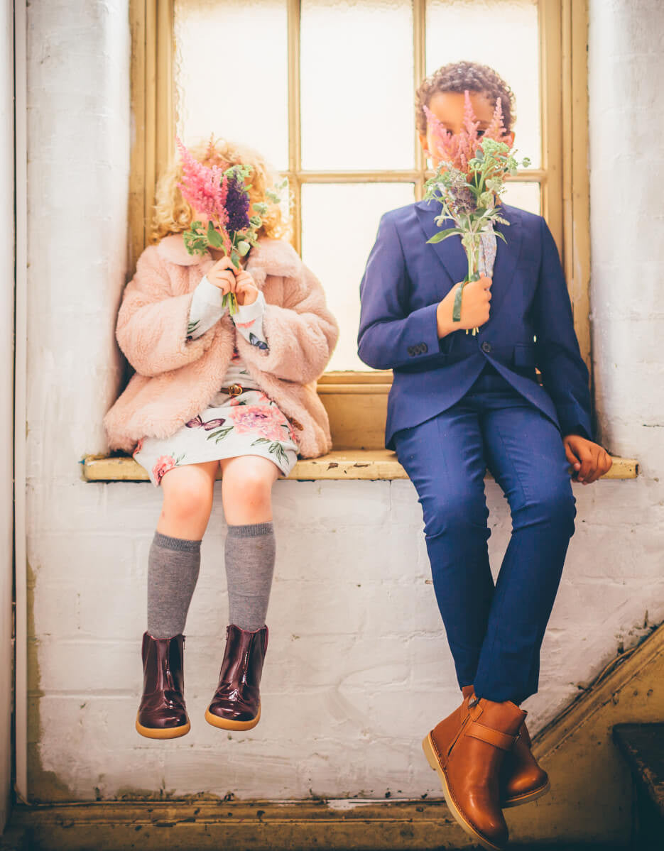 two children sat on window ledge with flowers covering face designer shoes