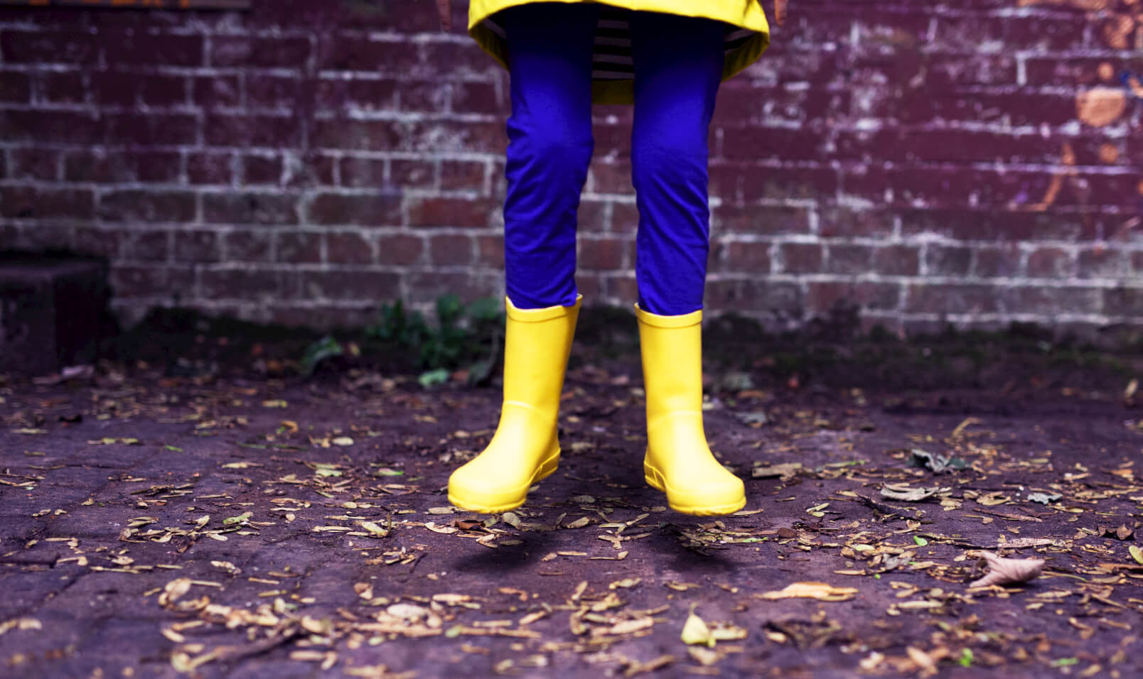 yellow wellies kid jumping raincoat