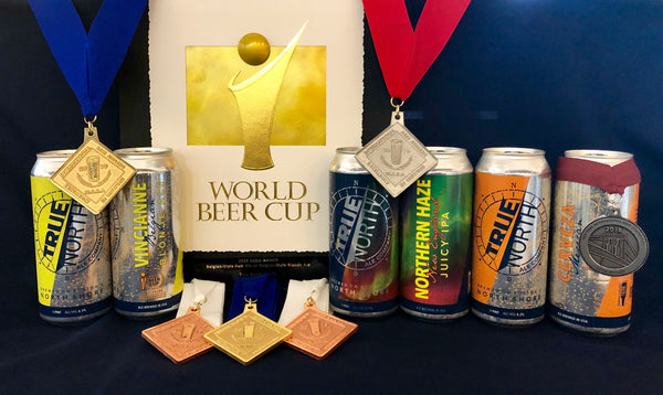 A display of awards that True North Ales has won, along with cans of the winning beers.