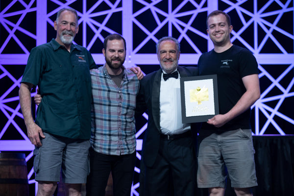 Founder Gary Rogers, Head Brewer Seth Barnum, and Founder Jake Rogers receiving the Gold Award for Vincianne, a Belgian Blonde Ale, from Charlie Papazian at the 2018 World Beer Cup