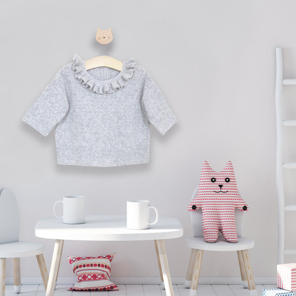 Grey Frill Neck Jumper hanging on wall