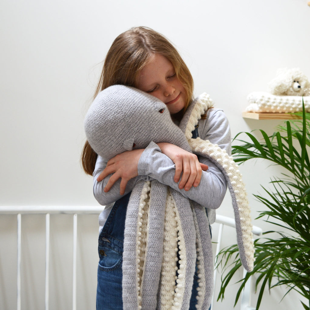 child cuddling large amigurumi octopus crochet kit, completed octopus in grey and white