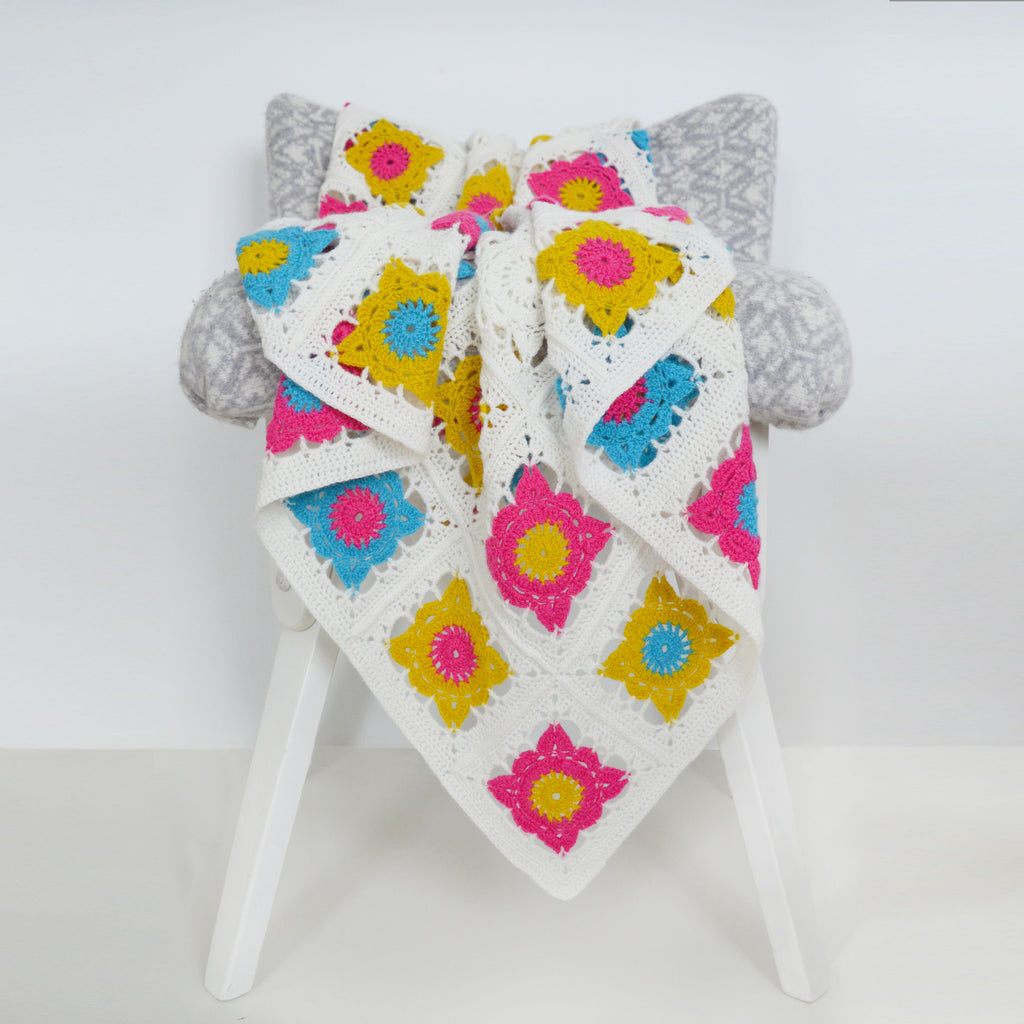 bright crochet square blanket on chair