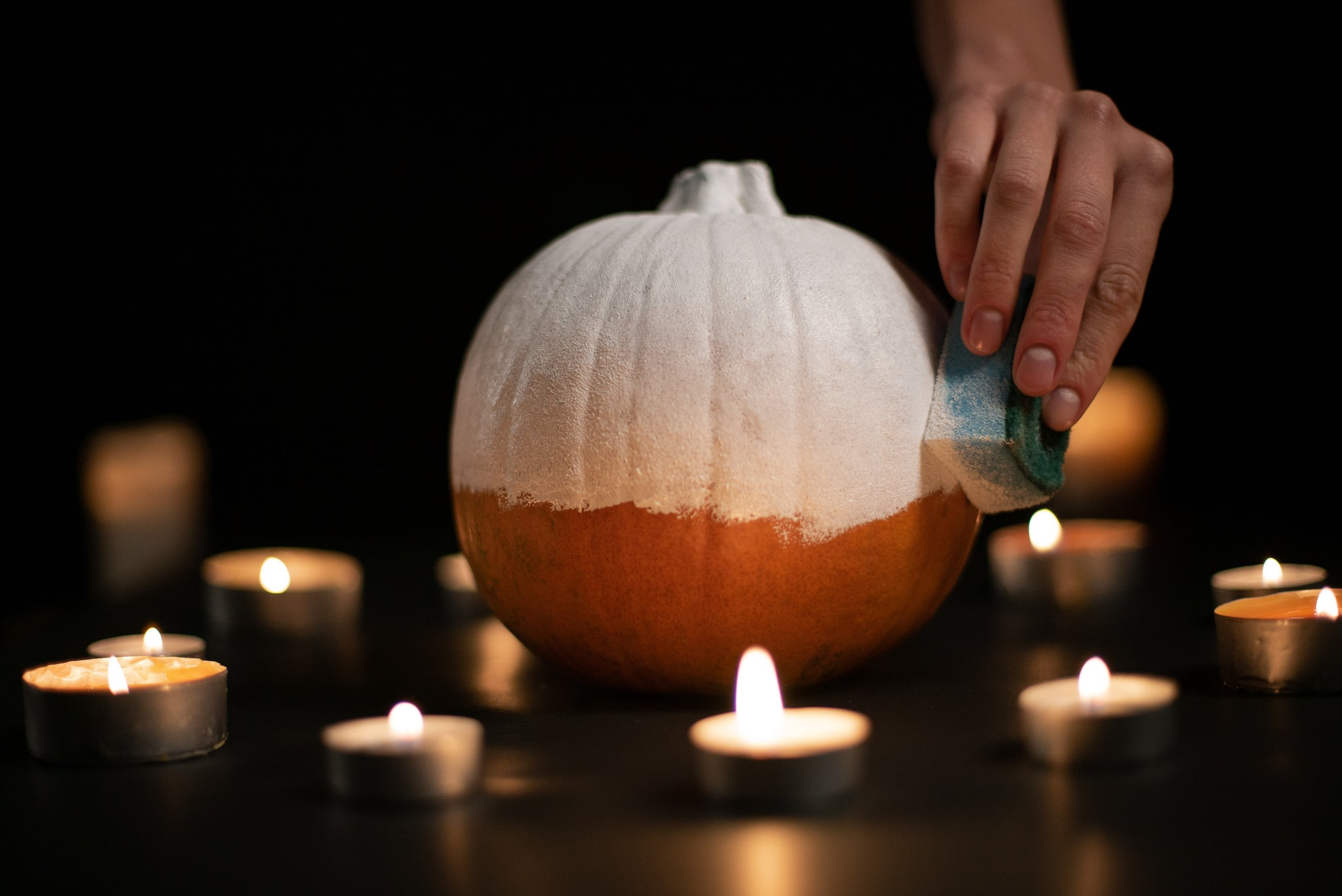 A sponge applicator is used to apply the white base coat to the entirety of the pumpkin.