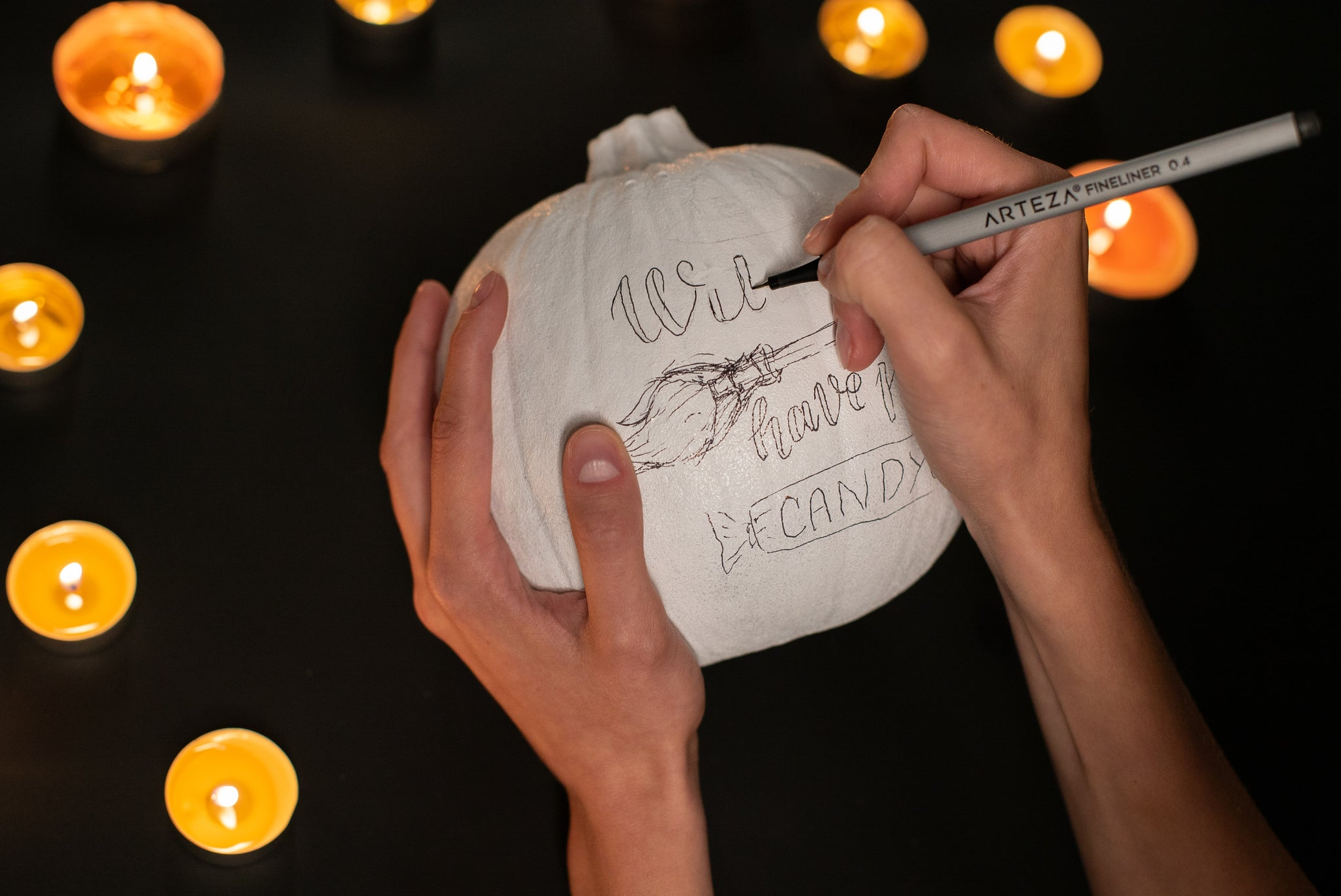 Drawing the design onto the pumpkin with a fineliner pen.