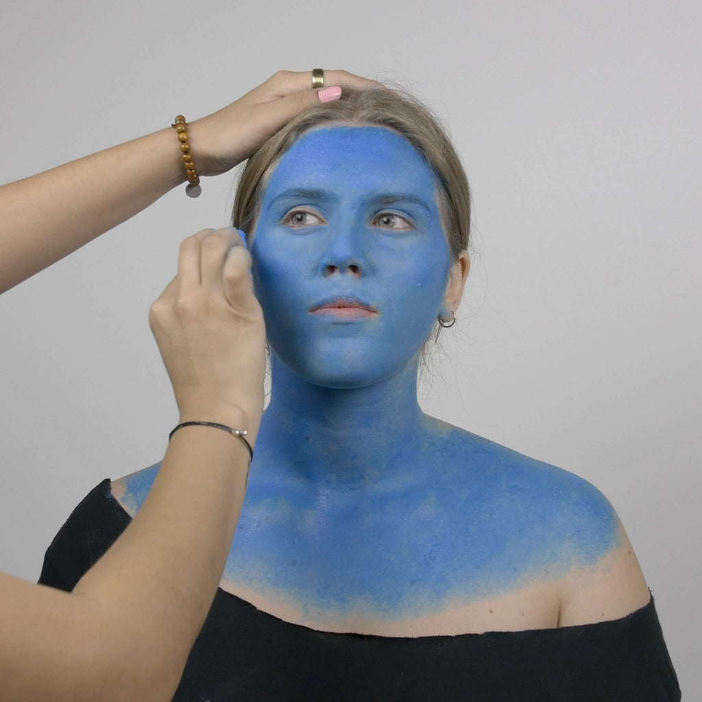 Blue face paint is added to the model's face, neck, and shoulders using a sponge applicator