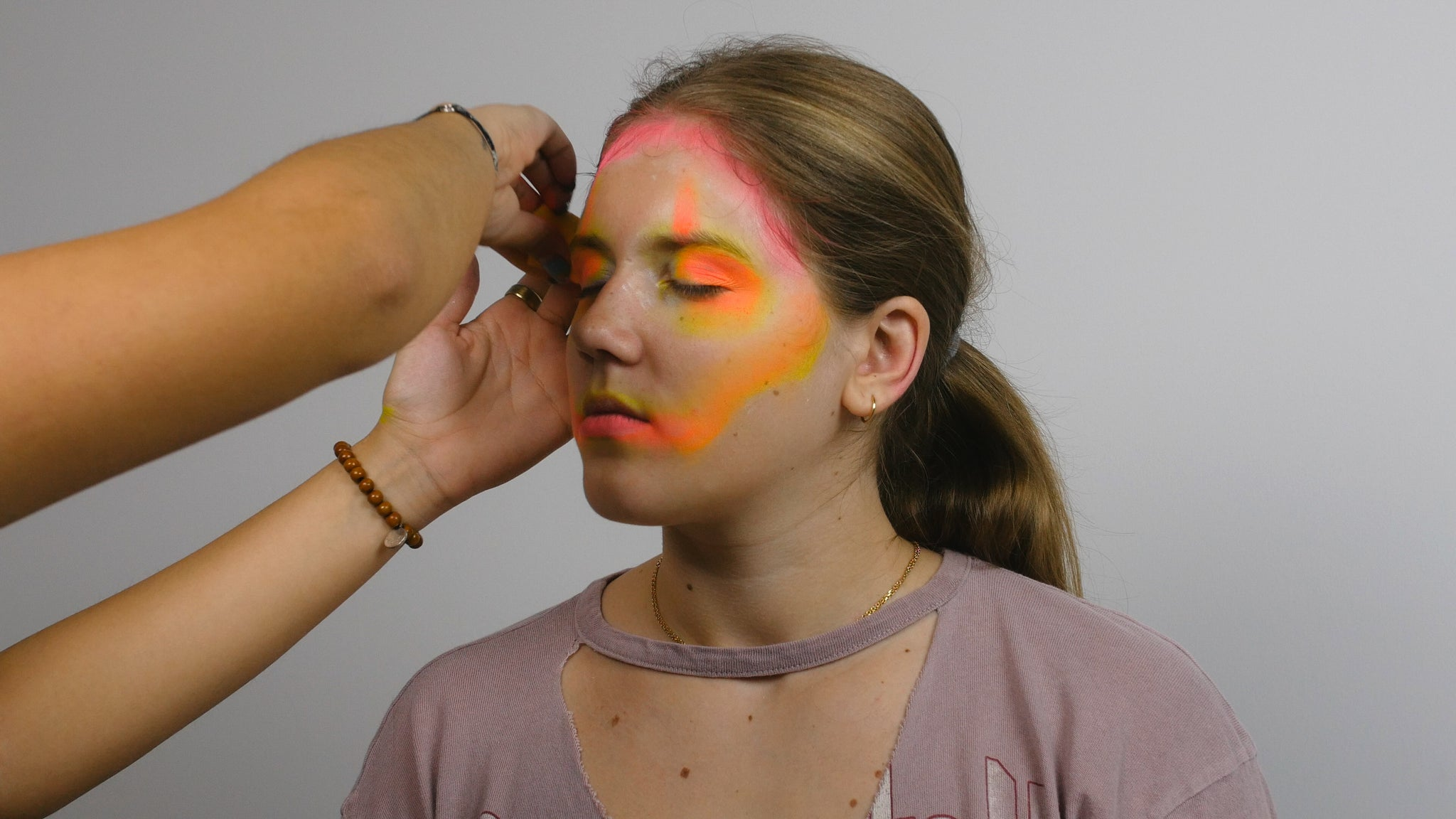 Apply Yellow and Orange Face Paint to Model's face around eyes and on cheek