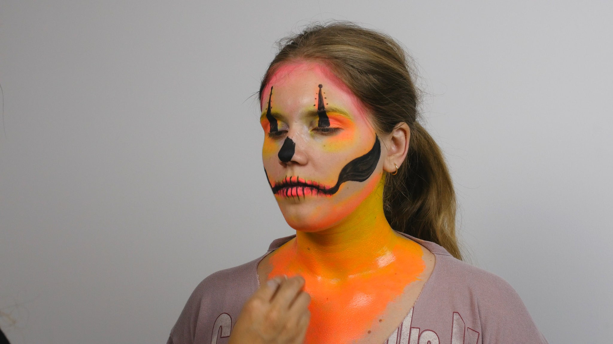 Use sponge to apply yellow and orange face paint to neck and chest area