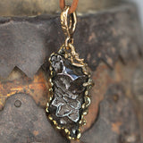 Meteorite set in bronze pendant.