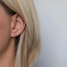Gold ear climber with hammered finish worn by blonde haired model