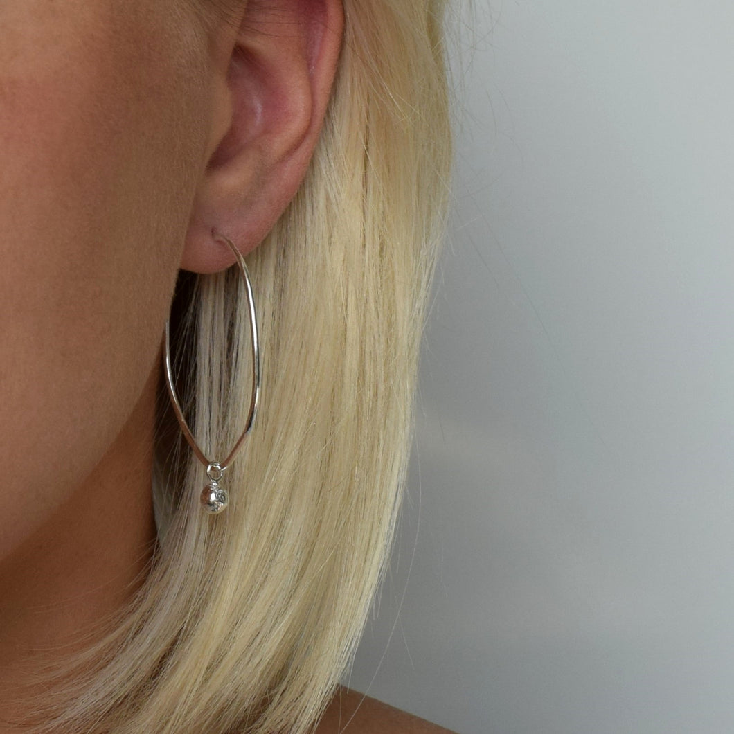 Silver oval hoop earrings with hanging silver ball worn by blond haired model