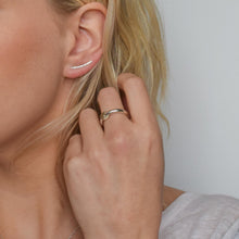 Hammered silver ear climber worn alongside silver and gold spinner ring on blond haired model