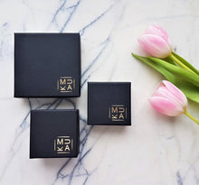 Stylish black cardboard jewellery boxes with gold MUKA studio logo in bottom right corner