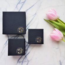 MUKA studio packaging, black jewellery boxes with gold logo placed on marble tile next to pink tulip flowers