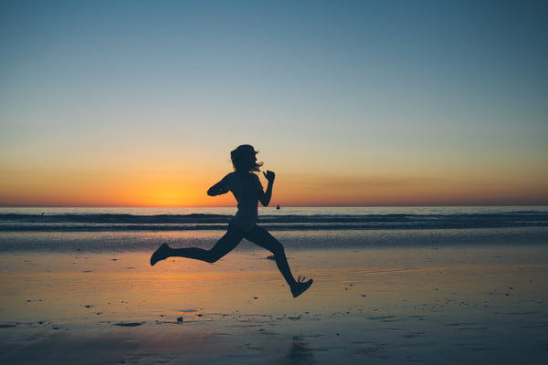 Girl Running in Sunset on Beach
