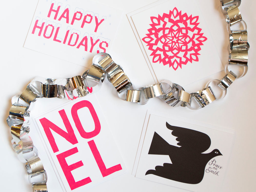 styled holiday cards from banquet workshop featuring neon and a peace dove