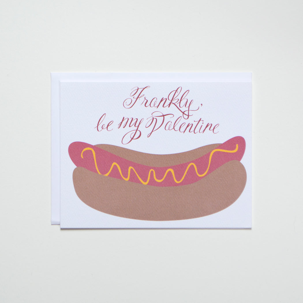 Frankly be my Valentine in hand lettered script with lots of flourishes, pictured with a hot dog and mustard in a bun.