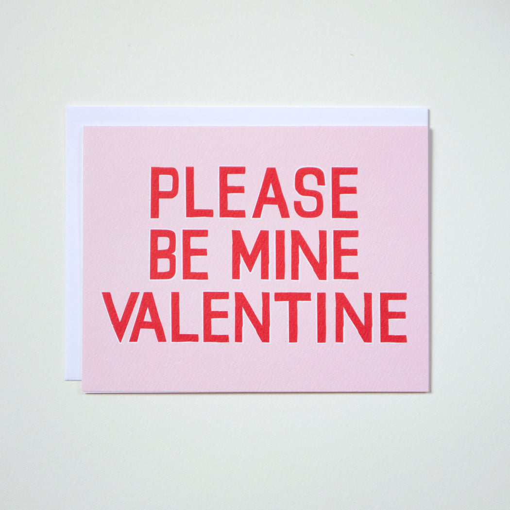 Red type on pale pink reads Please be Mine Valentine on a Note Card