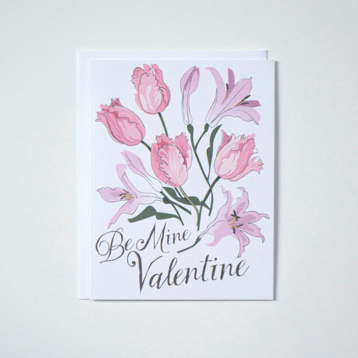 Valentine's note card with tulips and lillies in soft pinks reads be mine valentine at bottom