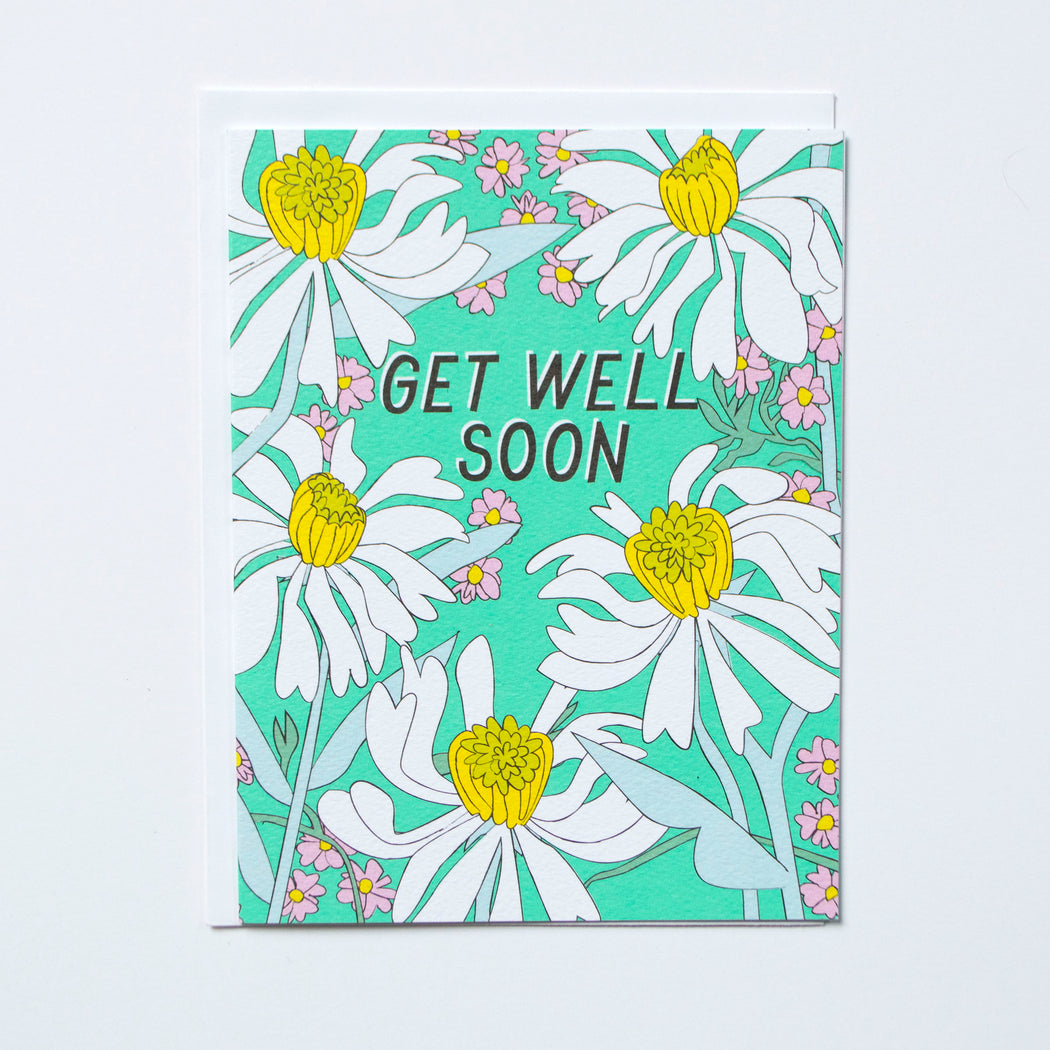 Get Well Soon written on a note card filled with daisies